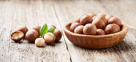 Macadamia nuts with leaves on wooden background