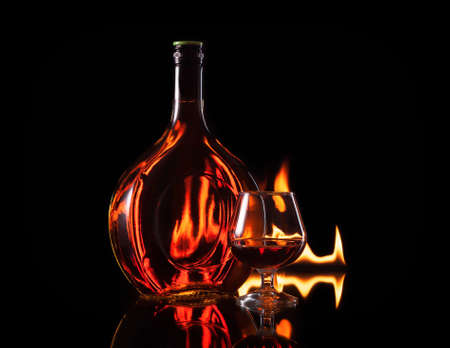 Bottle glass of cognac in fire flame on black background