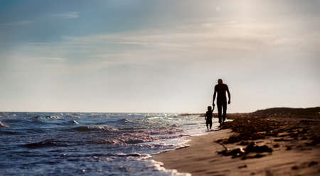 father and son to the sea at sunset photo