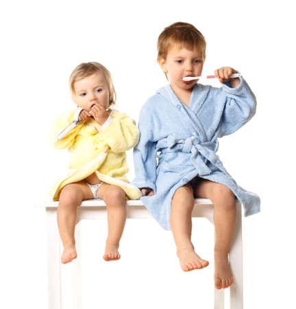 Beautiful kids preparing to brush their teeth wearing white bathrobes - isolated, closeup