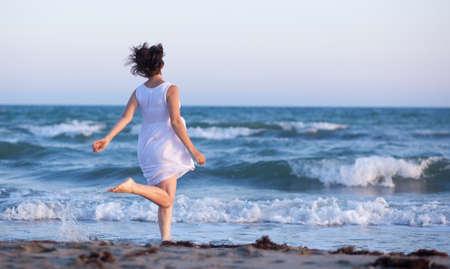 girl in white dress running along the beach photo