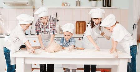 happy little chefs preparing dough in the kitchen Stock Photo