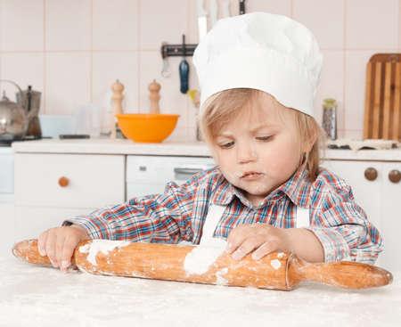 happy little girl making pizza dough