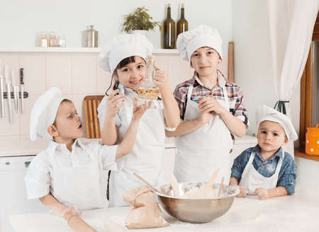 happy little chefs preparing dough in the kitchen photo