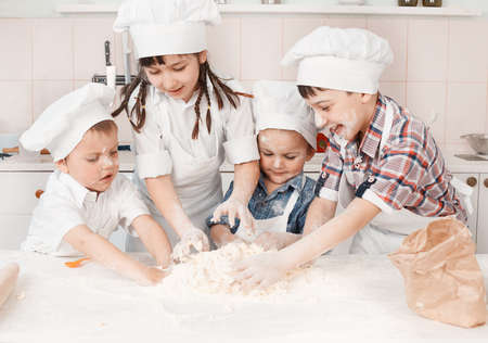 happy little chefs preparing dough in the kitchen photo