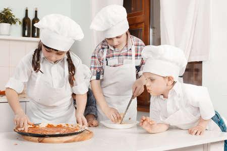 haciendo pan: Los ni�os en ropa cocineros
