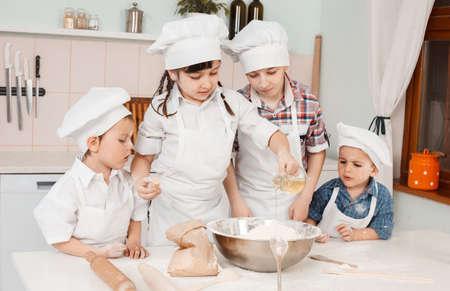 ni�os cocinando: peque�os chefs felices preparan la pasta en la cocina