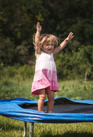 baby girl jumping on  trampoline photo