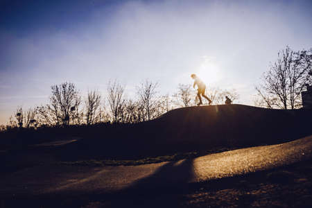 Silhouettes of children in the skate park at sunset Stock Photo