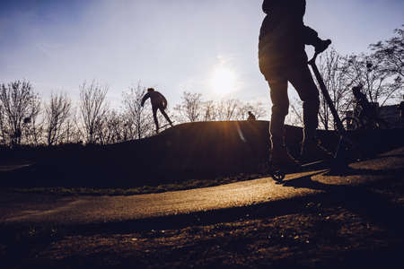 Silhouettes of children on scooters in the skate park at sunset