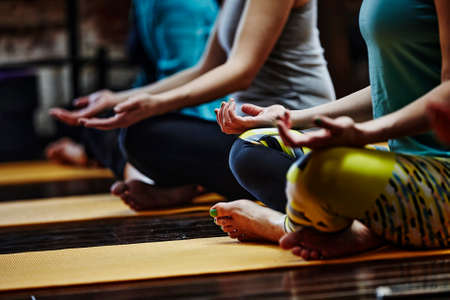 Yoga class people lifestyle with women group in lotus pose meditating in relax silence gym studio indoor.