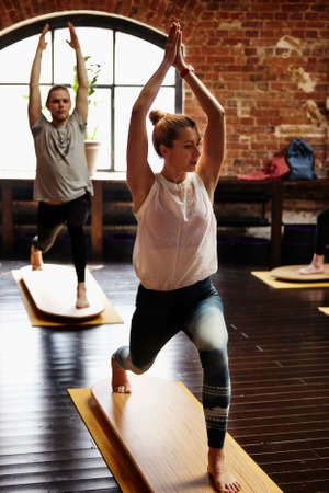 Group of young sporty people, man and woman practicing yoga lesson with instructor, working out, indoor close up image, studio on yoga board