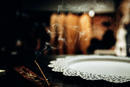 Close up of an Incense stick being lit and burning outside