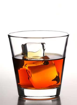 distilled water: Vaso de whisky con cubitos de hielo sobre fondo blanco