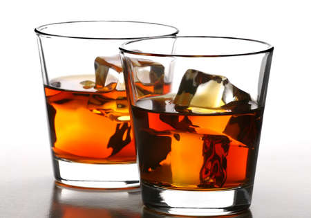 distilled: two glass of whiskey with ice cubes on white background
