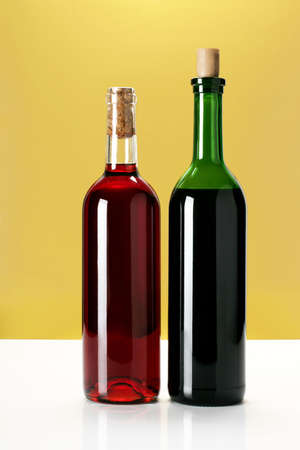 two bottles of wine on yellow background
