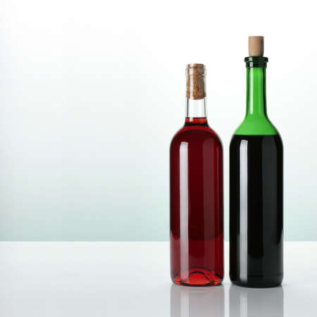 two bottles of wine on glossy surface photo