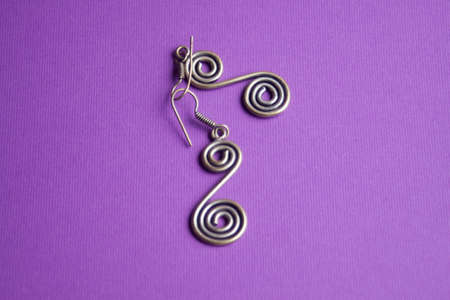 silver earrings in the form of a spiral on a purple background