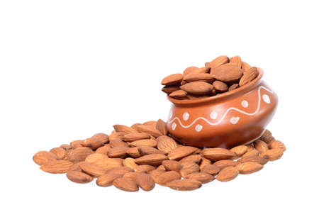 Almonds in a clay pot with heap isolated on a white background