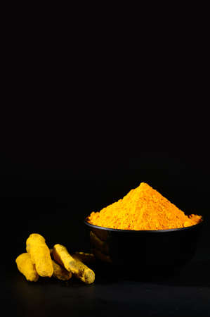 peppery: Turmeric powder and roots or barks in black bowl on black background