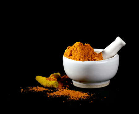 peppery: Turmeric powder in mortar with pestle and roots or barks on black background Stock Photo