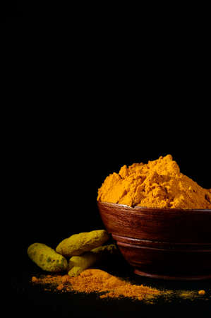Turmeric powder and roots or sticks in wooden bowl on black background Stock Photo