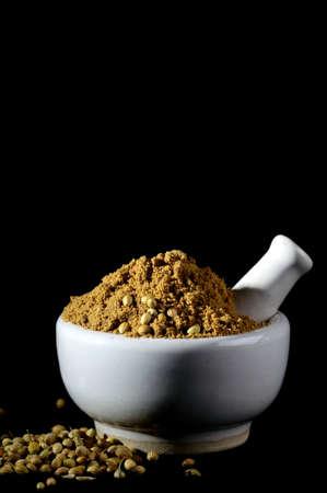 ollas de barro: Cilantro en polvo y semillas con mortero y mano sobre fondo negro.