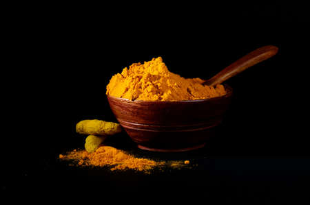 peppery: Turmeric powder and roots or sticks in wooden bowl on black background Stock Photo