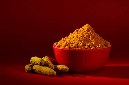 oleoresin: Dry Turmeric powder and roots or barks in red bowl on red background Stock Photo