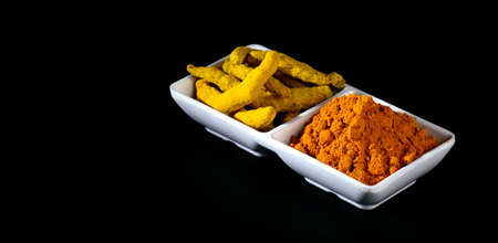 Dry Turmeric powder and roots or barks in white plate Stock Photo