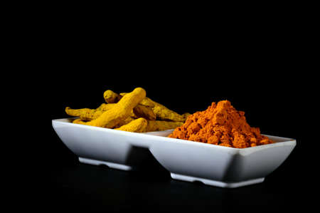 oleoresin: Dry Turmeric powder and roots or barks in white plate Stock Photo