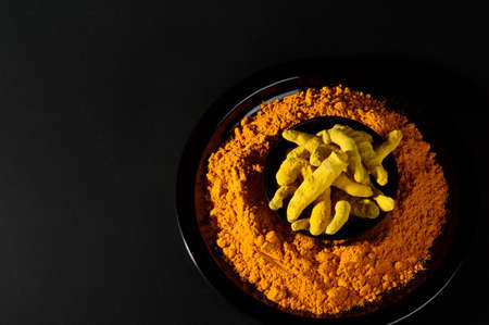 peppery: Turmeric powder and roots or barks on black background
