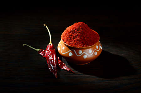 capsaicin: chilly powder in clay pot with red chilly, dried chillies on wooden background