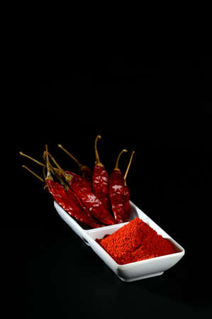 chilly powder with red chilly in white plate, dried chillies on black background