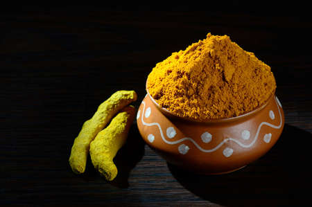 peppery: Turmeric powder in clay pot with roots or barks on black background Stock Photo