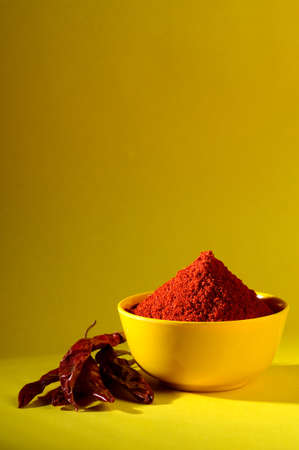 hottest: chili powder in yellow bowl on yellow background. Red chilly pepper Stock Photo