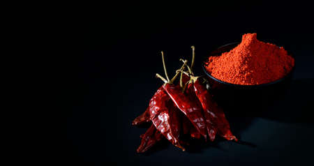 capsaicin: chilly powder in black bowl with red chilly, dried chillies on black background