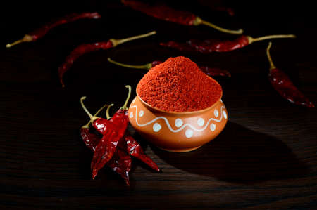 hottest: chilly powder in clay pot with red chilly, dried chillies on wooden background