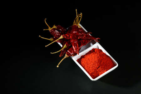 hottest: chilly powder with red chilly in white plate, dried chillies on black background