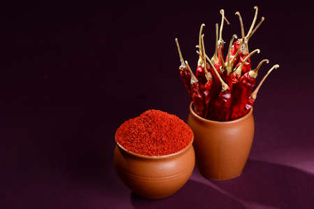 chilly powder with red chilly in clay pots, dried chillies on dark background Stock Photo