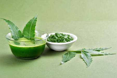 neem: Medicinal Neem leaves paste and juice with leaves on green background Stock Photo