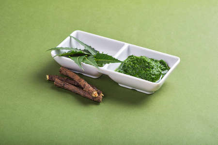 neem: Medicinal Neem leaves paste and leaves with twigs on green background Stock Photo