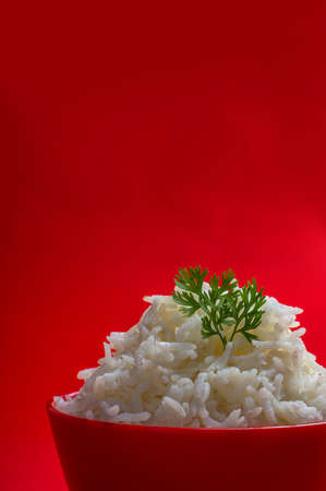 Cooked plain white basmati rice in a red bowl on red background Stock Photo