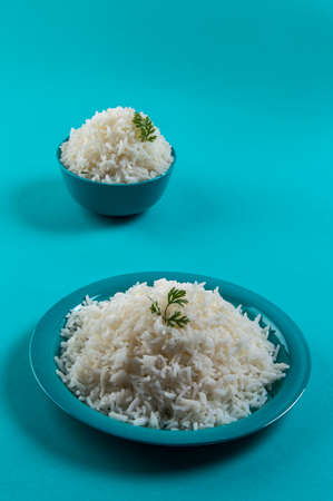 Cooked plain white basmati rice in a blue plate and bowl on blue background