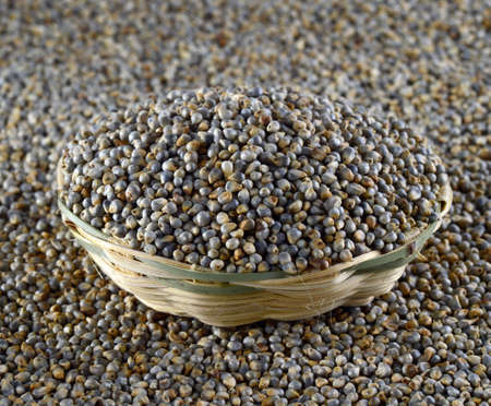 Bajra (Pearl millet) in wooden (bamboo) basket Stock Photo