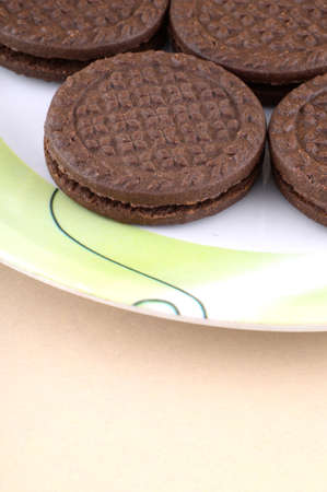 filling in: Brown chocolate sandwich biscuits with cream filling in plate