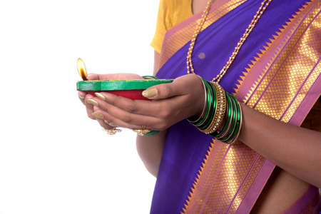 Portrait of a woman holding diya, Diwali or deepavali photo with female hands holding oil lamp during festival of light on white background