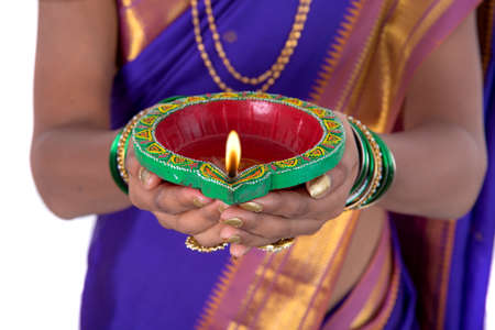 oil lamp: Portrait of a woman holding diya, Diwali or deepavali photo with female hands holding oil lamp during festival of light on white background