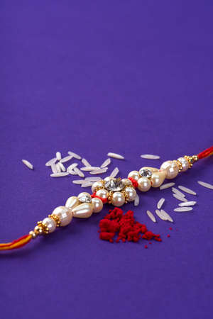 Raksha Bandhan : Rakhi with rice grains and kumkum. An Indian festive background. Traditional Indian wrist band which is a symbol of love between Brothers and Sisters.