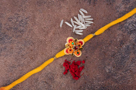 Raksha Bandhan : Rakhi with rice grains and kumkum on stone background, Traditional Indian wrist band which is a symbol of love between Brothers and Sisters. Stock Photo